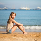 Mujer joven que se relaja en la playa Imagen de archivo libre de regalías