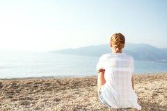 Mujer joven que se relaja en la playa por la mañana fotos de archivo