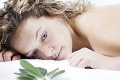 Mujer joven que se relaja en la toalla blanca Imagenes de archivo