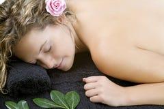 Mujer joven que se relaja en la toalla negra Fotos de archivo libres de regalías