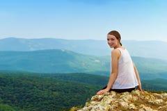 Mujer joven que se relaja en montañas Fotografía de archivo libre de regalías