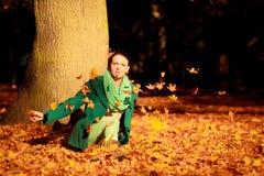 Mujer joven que se relaja en parque otoñal Imágenes de archivo libres de regalías