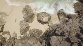 Mujer joven que se relaja en piedra y que salpica ondas del mar en la playa arenosa Mujer hermosa del paisaje aéreo en la playa t almacen de metraje de vídeo