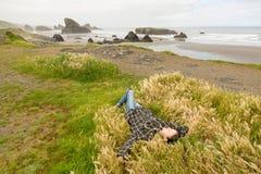 Mujer joven que se relaja en roca cerca del Océano Pacífico Fotos de archivo libres de regalías