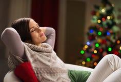 Mujer joven que se relaja en silla delante del árbol Imagen de archivo libre de regalías