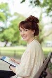 Mujer joven que se relaja en un banco de parque Fotografía de archivo