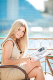 Mujer joven que se relaja en un café al aire libre Foto de archivo libre de regalías