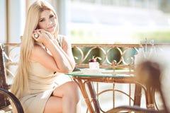 Mujer joven que se relaja en un café al aire libre Imagenes de archivo