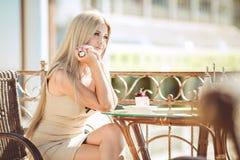 Mujer joven que se relaja en un café al aire libre Fotos de archivo libres de regalías