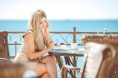Mujer joven que se relaja en un café al aire libre Imagen de archivo libre de regalías