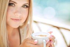 Mujer joven que se relaja en un café al aire libre Imágenes de archivo libres de regalías