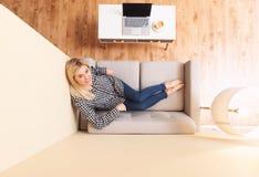 Mujer joven que se relaja en un sofá Imagen de archivo