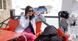 Mujer joven que se relaja en una estación de esquí alpina Fotos de archivo