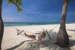 Mujer joven que se relaja en una hamaca por la playa Imagen de archivo