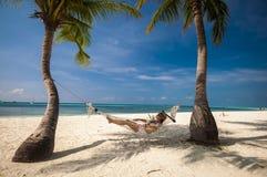 Mujer joven que se relaja en una hamaca por la playa Fotos de archivo