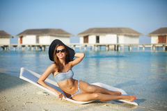 Mujer joven que se relaja en una silla de cubierta moderna en una playa tropical con el sombrero de paja y las gafas de sol elega fotografía de archivo