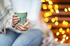 Mujer joven que se relaja mientras que bebe té en casa imagen de archivo libre de regalías