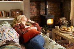 Mujer joven que se relaja por el fuego Fotos de archivo