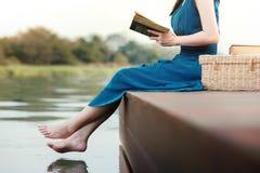 Mujer joven que se relaja por la orilla El sentarse en cubierta y el libro de lectura fotos de archivo libres de regalías