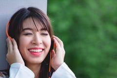 Mujer joven que se relaja y que canta mientras que música que escucha con el earp Imagenes de archivo