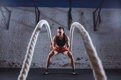 Mujer joven que se resuelve con las cuerdas de la batalla en gimnasio apto de la cruz imagenes de archivo
