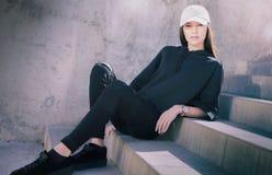 Mujer joven que se sienta afuera en los pasos que llevan la ropa de moda fresca Fotos de archivo libres de regalías