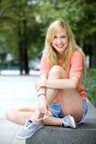 Mujer joven que se sienta al aire libre Imagenes de archivo
