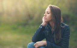 Mujer joven que se sienta al aire libre Fotos de archivo libres de regalías