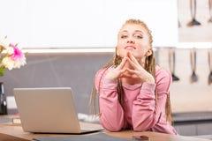 Mujer joven que se sienta al lado del ordenador Imagen de archivo libre de regalías