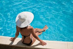 Mujer joven que se sienta cerca de piscina. Imagen de archivo libre de regalías