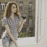 Mujer joven que se sienta cerca de ventana con un vidrio de vino Fotografía de archivo