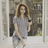 Mujer joven que se sienta cerca de ventana con un vidrio de vino Foto de archivo libre de regalías