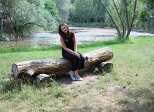Mujer joven que se sienta cerca del lago Fotos de archivo