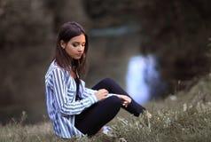Mujer joven que se sienta cerca del río Fotos de archivo libres de regalías
