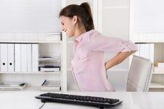Mujer joven que se sienta con dolor de espalda en la oficina foto de archivo