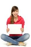 Mujer joven que se sienta con el cartel en blanco Imágenes de archivo libres de regalías