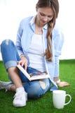 Mujer joven que se sienta con el libro en hierba Mujer joven 15 Fotografía de archivo