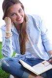 Mujer joven que se sienta con el libro en hierba Mujer joven 15 Foto de archivo libre de regalías