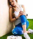 Mujer joven que se sienta con el libro en hierba Fotografía de archivo libre de regalías