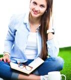 Mujer joven que se sienta con el libro en hierba Imagen de archivo libre de regalías