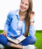 Mujer joven que se sienta con el libro en hierba Fotos de archivo