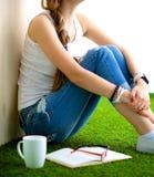Mujer joven que se sienta con el libro en hierba Imagenes de archivo