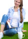 Mujer joven que se sienta con el libro en hierba Foto de archivo