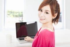 Mujer joven que se sienta con el ordenador portátil foto de archivo libre de regalías
