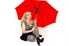 Mujer joven que se sienta con el paraguas rojo grande foto de archivo libre de regalías