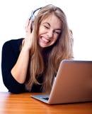 Mujer joven que se sienta con la computadora portátil Imagen de archivo libre de regalías