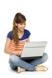 Mujer joven que se sienta con la computadora portátil Imágenes de archivo libres de regalías