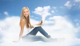 Mujer joven que se sienta con la computadora portátil Fotografía de archivo libre de regalías