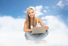 Mujer joven que se sienta con la computadora portátil Fotos de archivo libres de regalías