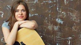 Mujer joven que se sienta con la guitarra Foto de archivo libre de regalías